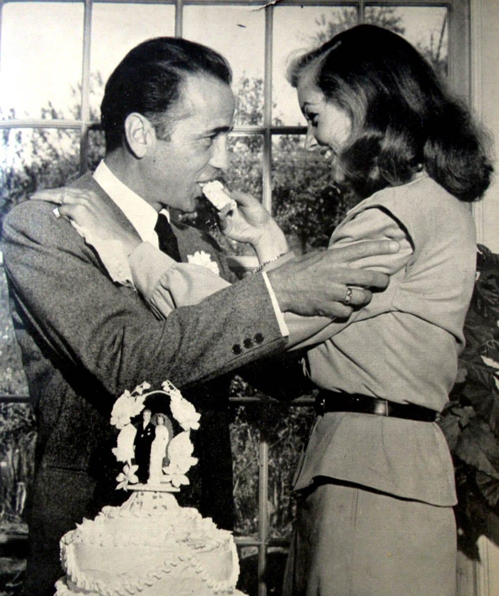 "Humphrey Bogart and his wife Lauren ""Betty"" McCall eating cake"
